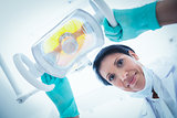 Low angle of female dentist adjusting light