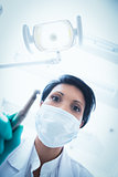 Female dentist in surgical mask holding dental drill