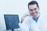Smiling male dentist with computer
