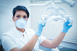 Demale dentist in surgical mask adjusting light