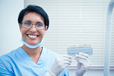 Smiling female dentist holding teeth model