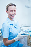 Female dentist in blue scrubs holding tray of tools