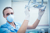 Portrait of dentist adjusting light