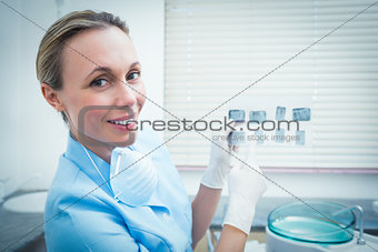 Portrait of female dentist holding x-ray