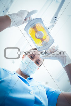 Portrait of female dentist adjusting light