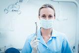 Female dentist in surgical mask holding dental tool