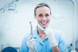 Female dentist holding dental tool