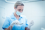 Female dentist in surgical mask holding dental tools