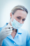 Female dentist in surgical mask holding injection
