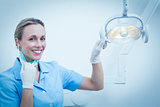 Smiling female dentist adjusting light