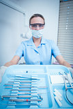 Female dentist in surgical mask holding tray of tools