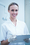 Smiling female dentist holding clipboard