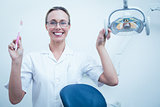 Smiling female dentist holding toothbrush