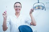 Smiling female dentist holding toothbrush