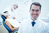 Smiling male dentist with assistant examining womans teeth