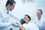 Male dentist shaking hands with woman