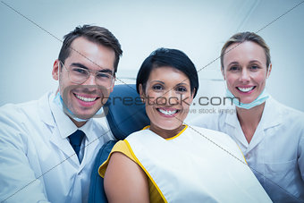 Portrait of smiling dentist and assistant with female patient
