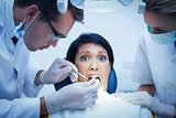 Dentist with assistant examining womans teeth