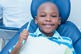 Boy holding toothbrush in the dentists chair