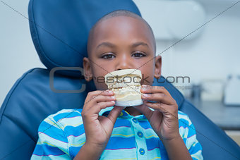 Portrait of smiling boy holding mouth model