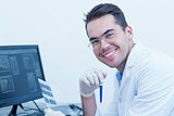 Male dentist with x-ray on computer