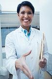 Smiling female dentist offering handshake