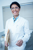 Smiling female dentist holding folder