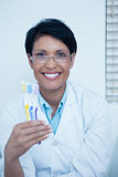 Smiling female dentist holding toothbrushes