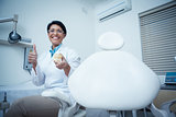 Dentist gesturing thumbs up while holding mouth model