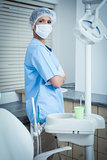 Dentist wearing surgical mask with arms crossed