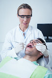 Female dentist examining mans teeth