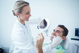 Female dentist brushing mans teeth