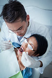 Male dentist examining womans teeth