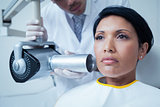 Serious young woman undergoing dental checkup