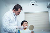 Male dentist brushing womans teeth