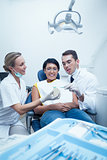 Dentists showing woman prosthesis teeth