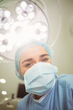 Young surgeon looking down at camera