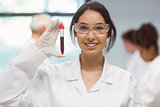 Pretty science student smiling and showing vial