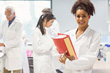 Science student holding large folder in lab