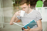 Student drinking a hot drink and holding book