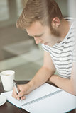 Smiling student sitting with a hot drink and writing on notepad