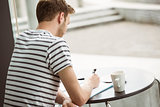 Student sitting with a hot drink and writing on notepad