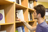 University student choosing books on bookshelves