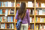University student standing in the bookcase