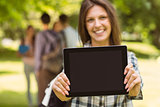 Smiling student with a shoulder bag and showing screen at tablet pc