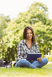 Smiling student sitting and using tablet pc