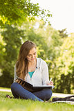 Smiling university student sitting and writing on notepad