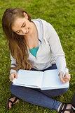 Smiling university student sitting and writing on notepad