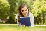Smiling university student lying and using tablet pc