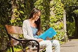 Smiling student sitting on bench and reading book
